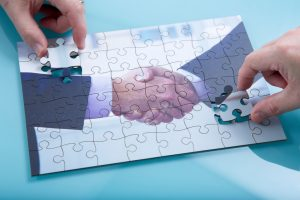 A jigsaw of a handshake being completed by two hands.