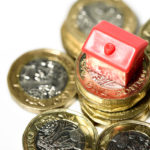 Macro close up of a Miniature house resting on new pound coins