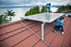 Men working on a solar panel on a roof