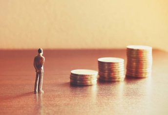 Miniature people looking future with stack coin about financial and money savings concept.