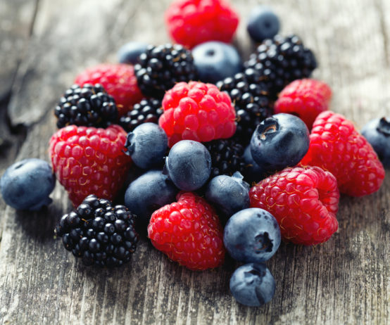 Strawberries, raspberries and blueberries on wooden surface