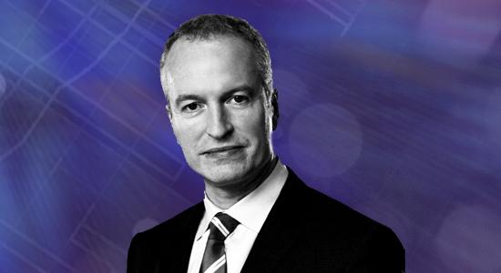 A headshot of Neil Harper on a purple background