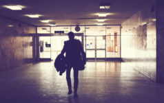 Silhouette of man walking through an empty hallway.