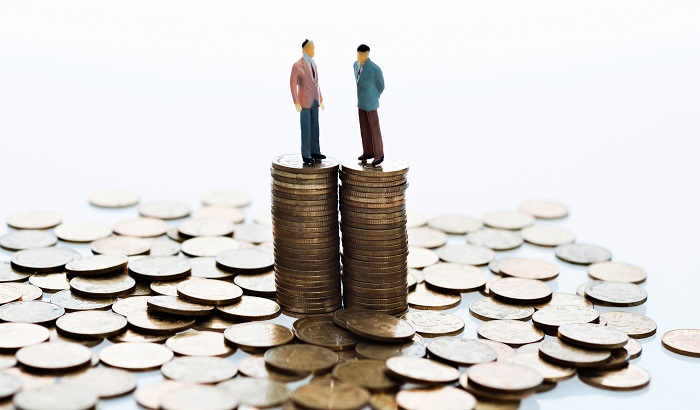 Two models stand on a pile of coins