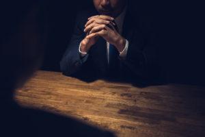 Detective interviewing subject in dark room