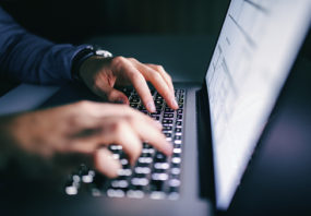 Close up of hands typing on laptop. Night work concept, private equity, survey, ernst & young
