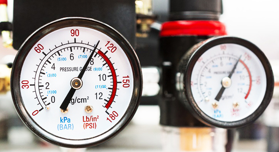 Two industrial manometers show almost critical pressure on the pump.