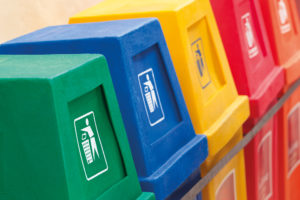 A row of recycling bins in different colors at a recycling station.