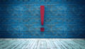 Exclamation mark symbol on blue brick wall, warning, caution