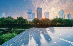 Solar Power Plant in modern city in sunset