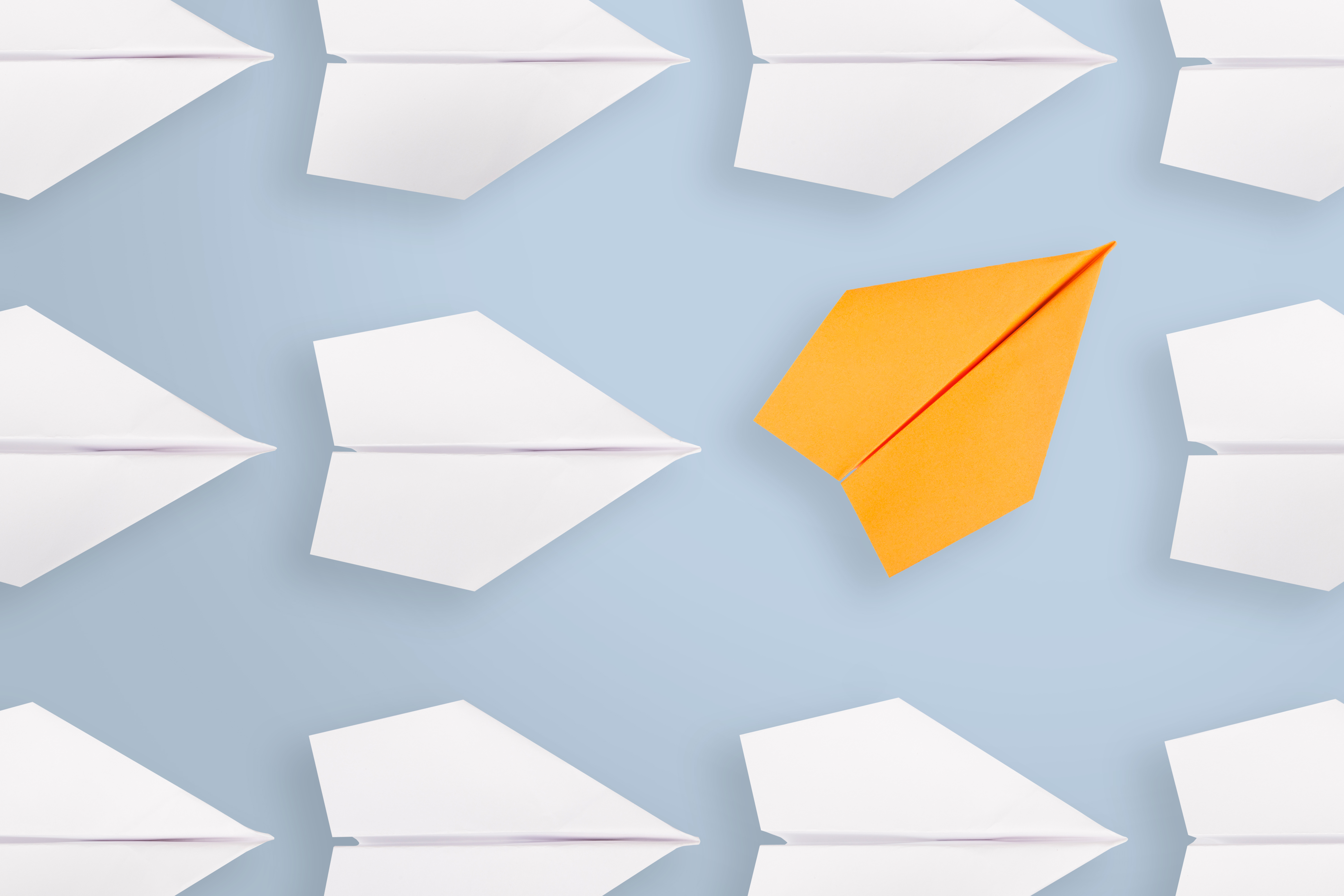 Change concepts with orange paper airplane leading among white