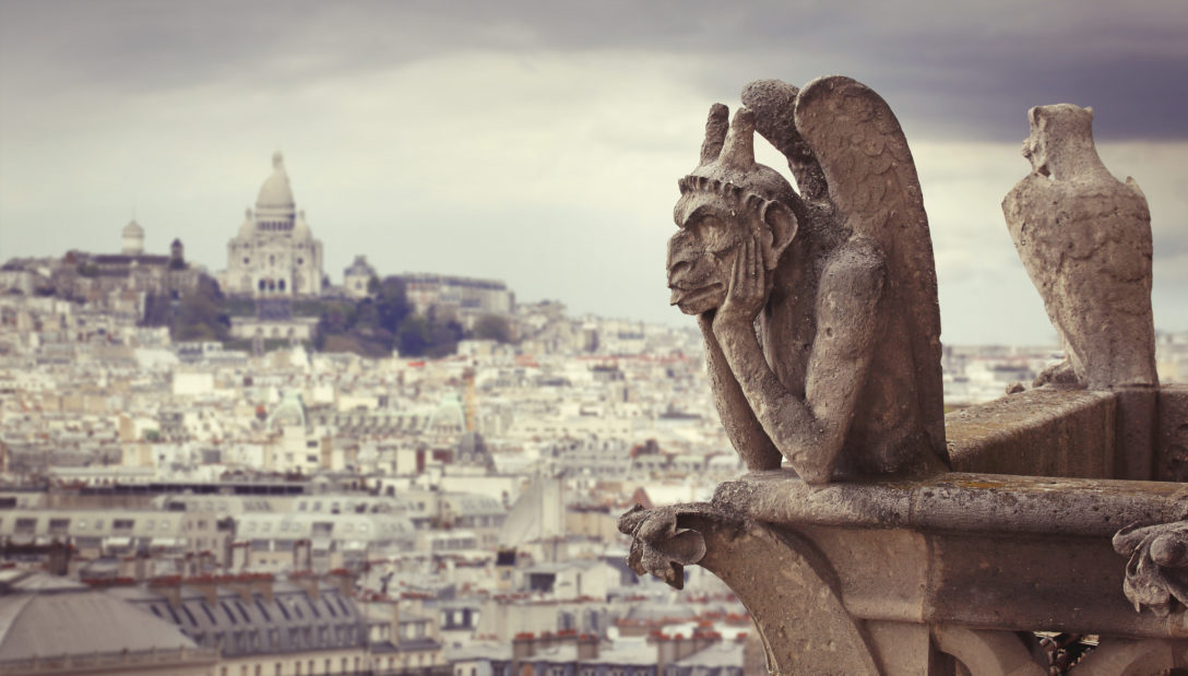 Le Stryge Chimera sculpture overlooks Paris from Notre Dame cathedral with Sacre Coeur basilica on the background