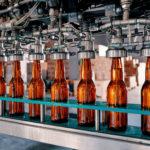 Bottles filling on the conveyor belt in factory