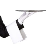 Close up of a waiter holding silver tray, white glove
