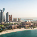 Aerial view of skyscrapers in Corniche bay in Abu Dhabi, UAE. Turquoise water in the front and blue sky in the distance combined with building exterior in the middle.