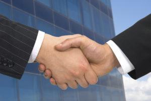 Handshake in front of office - iStock